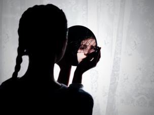 Una joven mujer se ver reflejada en un espejo roto