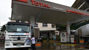 A worker anchors the roof of a fuel station to a mixer truck as Super Typhoon Mangkhut approaches the city of Tuguegarao