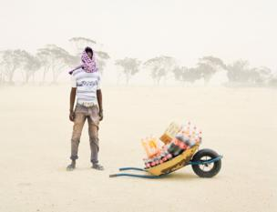 A man stands in the desert with a wheelbarrow of soft drinks