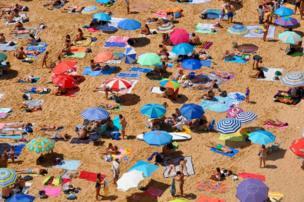 Toallas y sombrillas de colores en una playa.