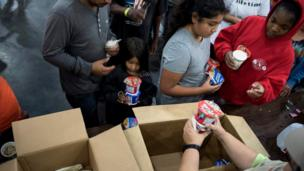 Flood victims receive food at a shelter in the George R. Brown Convention Center