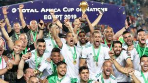 اللاعب رياض محرز يحمل كأس البطولة، وسط فريق الجزائر المحتفي بفوزه للمرة الثانية بكأس الأمم الأفريقية.