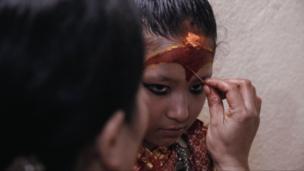 مادر کوماری، در حال آرایش دخترش قبل از اینکه عابدان به زیارتش بیایند.