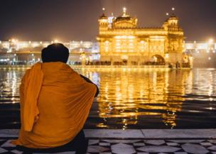 A man looks out on the Golden Temple with his back to us.