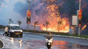 Bir motosikletli yangından uzaklaşıyor.
