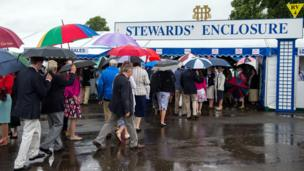 Visitors gather outside the Stewards' Enclosure, clearly not put off by the wet weather.
