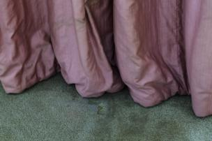 A pink curtain touches a grubby carpet.