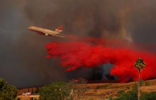 A DC-10 aircraft drops fire retardant on a wildfire in Orange, California, 9 October
