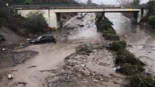 US Highway 101 at the Olive Mill Road overpass flooded with runoff water from Montecito Creek and blocked with mudflow and debris following heavy rains in Montecito, California.