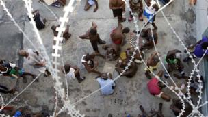 Some prisoners play dominoes, checkers or card games, during recreation time inside the National Penitentiary in downtown Port-au-Prince