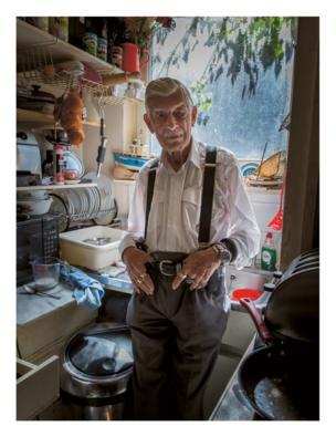 An elderly man stands in his kitchen