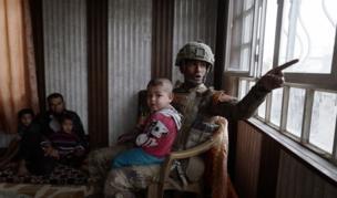 الملازم أول علاء يجلس مع مجموعة من المدنيين في كوكجلي. ومن المتوقع أن تستغرق عمليات الموصل أسابيع إن لم يكن شهورا