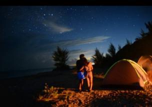 Una pareja acampando y mirando el cielo en la noche.