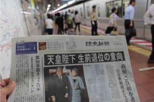 A Japanese newspaper with a story about reports the Emperor might abdicate on its front page, being held up for the camera in front of a view of people boarding a metro train in Tokyo. 14 July 2016.