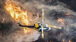 A helicopter flies over wildfires.