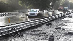 An emergency vehicle makes its way through mud on Highway 101 after heavy rains caused deadly mudslides in Montecito, California.