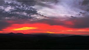 Sun rising from behind Mount Keen