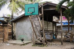 شبكة كرة سلة ولوحتها الخلفية في فناء خلفي لأحد المنازل