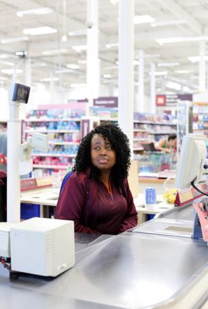 A Sainsbury cashier sits behind the cash desk.