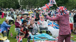 "Joseph Afrane, 52, in Union Jack clothing waves flags as members of the public in Green Park gather for a picnic and watch The Queen""s Patronage on a big screen during ""The Patron's Lunch"" celebrations"