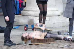 A man lies on a bed of nails as part of a street performance