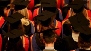 students at graduation ceremony up in caps n' gowns