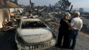A couple assess the damage caused by the wildfires.