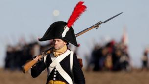 A history enthusiast, dressed as a soldier, marches before the re-enactment of the battle