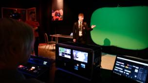 Young Reporter trying weather presenting in front of a green screen
