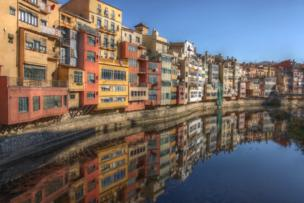 colourful houses are reflected in the river