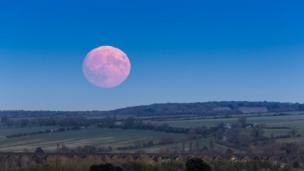 A reddish moons rises over the Harringworth Viaduct