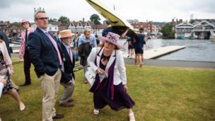 Spectators duck under rowing boats