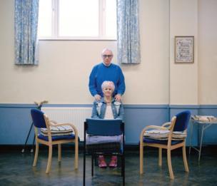 امرأة تجلس وخلفها رجل يضع يده على كتفها