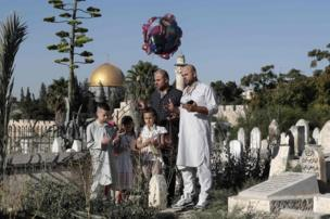 Palestinians pray over the grave of a loved one at a Muslim cemetery near the Al-Aqsa Mosque compound in Jerusalem's Old City, 25 June