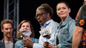 Rose McGowan and Clarke Peters with paper roses given for taking part