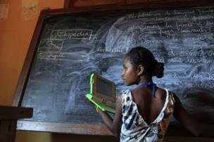 Madagascar, 2012. A girl stands with a laptop next to a black board
