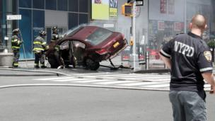 A red car is tilted on its side after striking pedestrians in New York