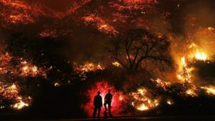 Firefighters monitor a section of the Thomas Fire along the 101 freeway on December 7, 2017 north of Ventura, California.