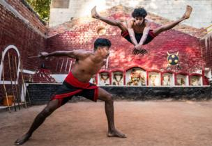 Two men perform a martial arts sequence, one draws his knife as the other leaps high into the air, splitting his legs apart as to avoid it