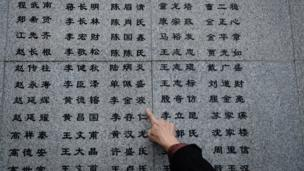 """侵華日軍南京大屠殺遇難同胞紀念館一名遇難者遺屬指著""""哭牆""""上新增的姓名(新華社圖片10/12/2016)"""