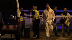 Police officers, one in a forensic suit