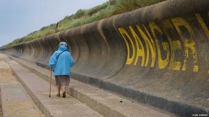 Woman walking along the coastline