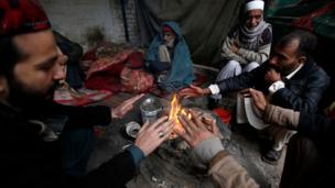 People sit around a fire to beat the cold weather in Peshawar, Pakistan, 04 January 2017. EPA/ARSHAD ARBAB