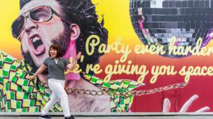 Mujer danzando frente a una pancarta