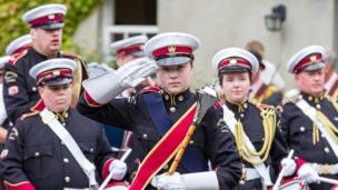 A young woman in a band make a salute while on parade