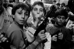 مجموعة من الأطفال يلوحون بمسدسات للمصور.