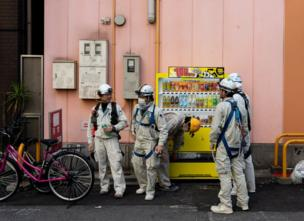 workmen with helmets and body suits grab a drink from a vending machine