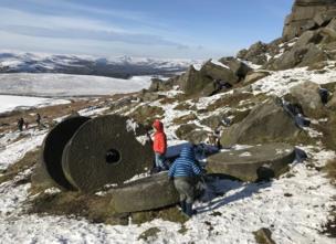 Niños jugando entre ruedas de piedra en la nieve.
