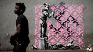 A man walks past a recent artwork by street artist Banksy in Paris