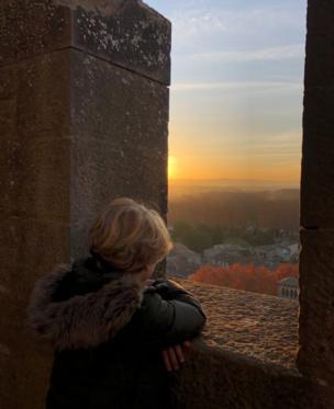 A boy looks at a sunset